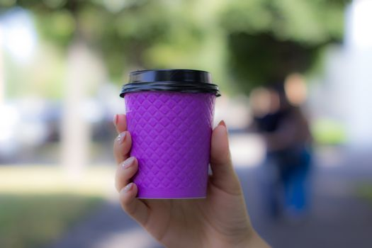 Purple cardboard Cup for coffee in a woman's hand