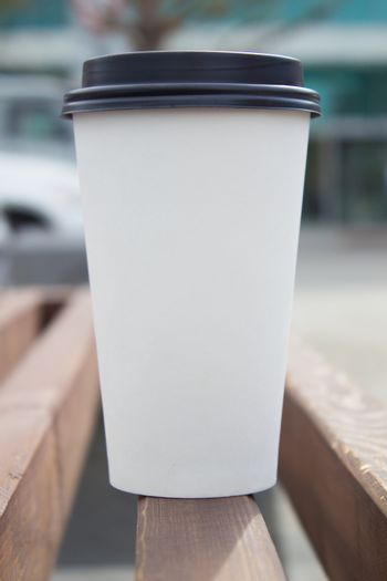 Breakfast and coffee theme: white paper coffee Cup with black plastic lid, outside. Coffee advertising
