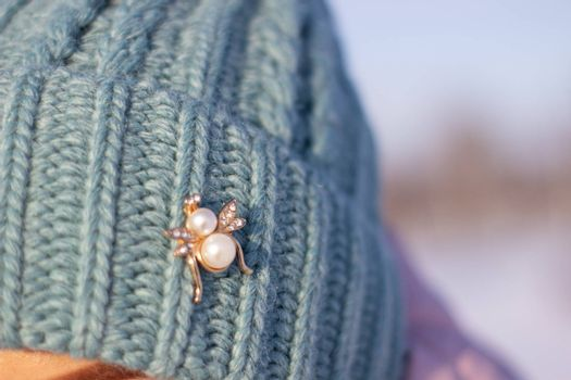 A woman in a knitted, turquoise winter hat.