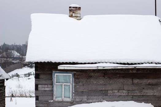 Wooden house in winter in the snow. A house with a chimney and a stove.