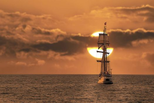 Antique tall ship, vessel leaving the harbor of The Hague, Scheveningen under a warm sunset and golden sky