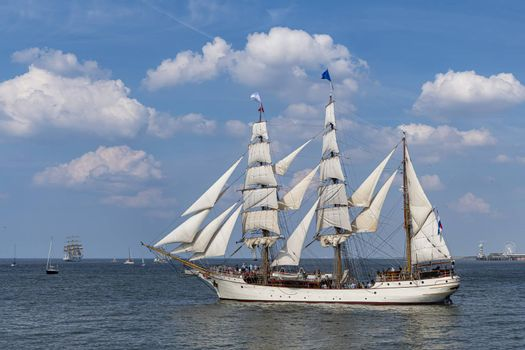 Antique tall ship, vessel leaving the harbor of The Hague, Scheveningen under a sunny and blue sky