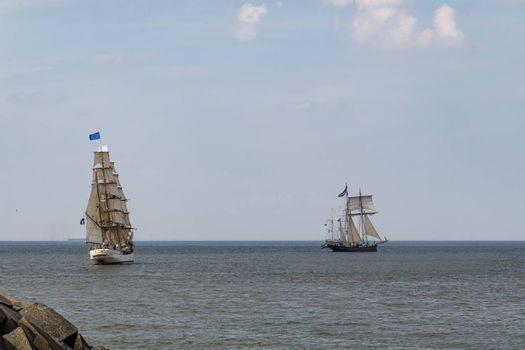 Antique tall ships, vessels leaving the harbor of The Hague, Scheveningen under a sunny and blue sky