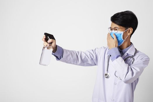 Asia doctor using spray alcohol cleaning for protect anti virus bacteria.  Preventive measures against corona virus.