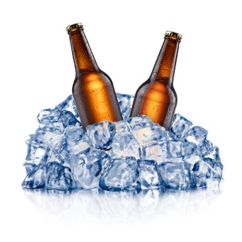 Two brown beer bottles, cooling down in a rough crushed ice. Clipping paths
