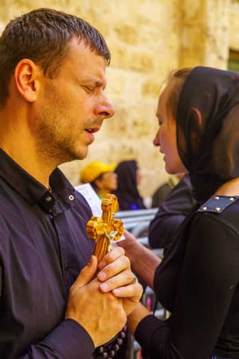 Jerusalem, Israel - April 6, 2018: Orthodox good Friday scene in the entry yard of the church of the holy sepulcher, with pilgrims praying. The old city of Jerusalem, Israel