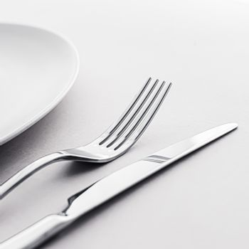 Empty plate and cutlery as mockup set on white background, top tableware for chef table decor and menu branding design