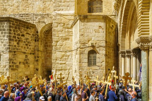 Jerusalem, Israel - April 6, 2018: Orthodox good Friday scene in the entry yard of the church of the holy sepulcher, with pilgrims carrying crosses. The old city of Jerusalem, Israel