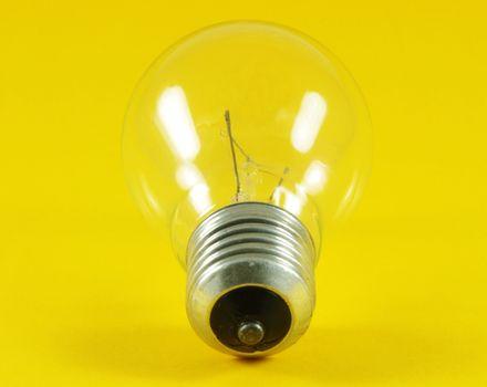 Light bulb closeup over yellow surface