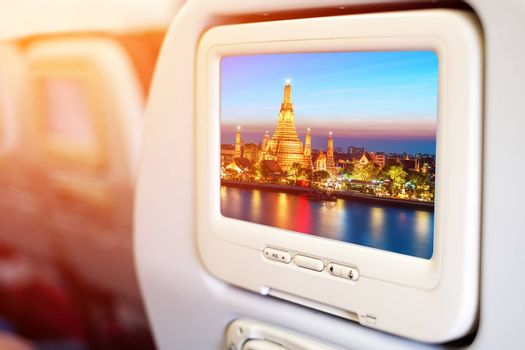Aircraft monitor in passenger seat on Wat Arun night view Temple in bangkok, Thailand background