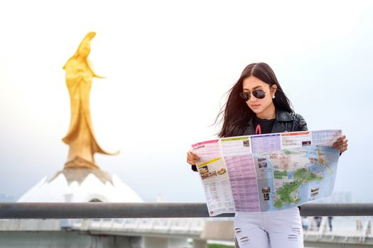 MACAU - JANUARY 11, 2016: Young female tourist with map looking for a way to Statue of kun iam in Macau. It is a popular tourist attraction of Asia.