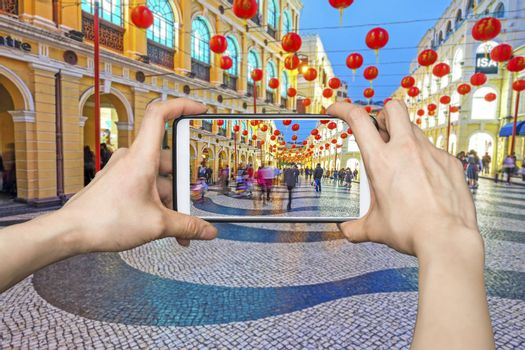 Girl taking pictures on mobile smart phone in Senado Square nigth view of Macau.