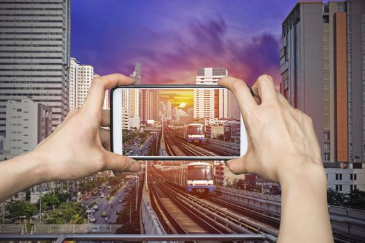 Girl taking pictures on mobile smart phone in Sky Train at bangkok,thailand