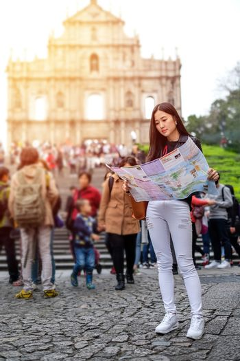 MACAU - JANUARY 11, 2016: Young female tourist with map looking for a way to View of the Ruins of St. Paul's Cathedral in Macau. It is a popular tourist attraction of Asia.