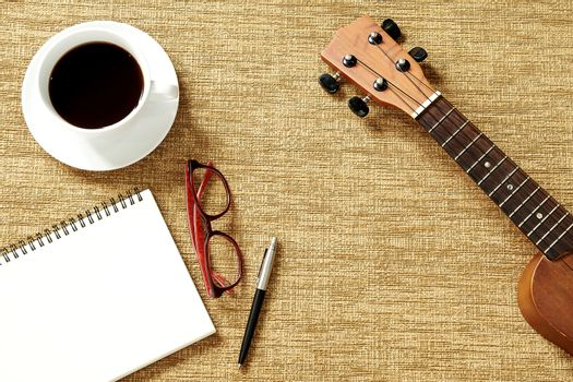 Top view of ukulele, notebook, pen, coffee cup and glasses on brown background