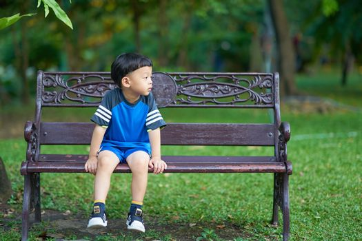 Thai boy sit on bench in park with green botany background