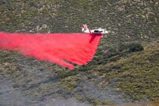 Winchester, CA USA - June 14, 2020: Cal Fire aircraft drops fire retardant on a dry hilltop wildfire near Winchester, California.