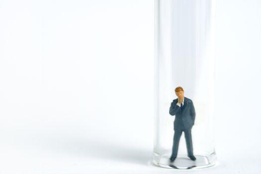 Health conceptual miniature people photography – testing specimen, a businessman on a laboratory tube. Image Photo