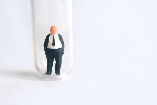 Health conceptual miniature people photography – testing specimen, a businessman on a laboratory test tube