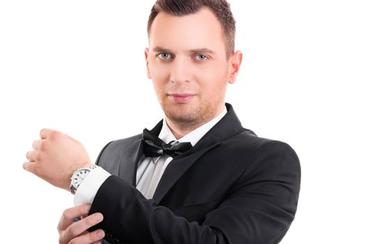 Portrait of a confident attractive young man in black suit with bow tie, adjusting the cufflinks on his white shirt, looking at the camera, isolated on a white background.