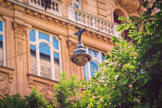 Close-up of a street lamp on aerial wires above green trees and a beautiful old building in the background. Hanging street light in Budapest city center.