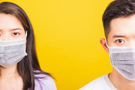 Asian beautiful woman and handsome man wearing protection face mask against coronavirus, looking to camera, studio shot isolated on yellow background with copy space, COVID-19 or corona virus concept