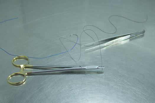 Scissors, tweezers and thread for stitches on metal table.