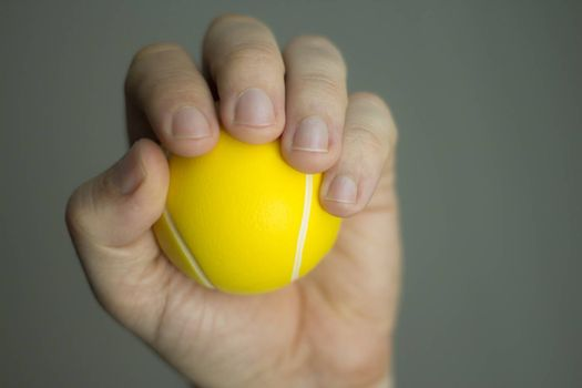Man hand squeezing an exercise ball physiotherapy