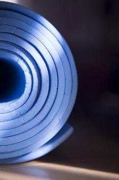 Old blue yoga mat rolled up on the floor. Fotografía de Gema Ibarra. Prohibida su utilización para cualquier uso sin autorización.Todos los derechos reservados.