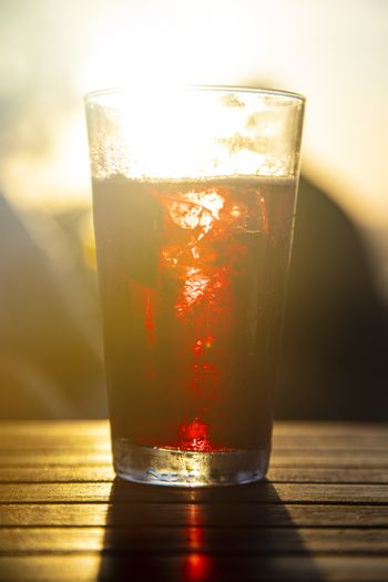 Red wine against the sun with male silhouette at background