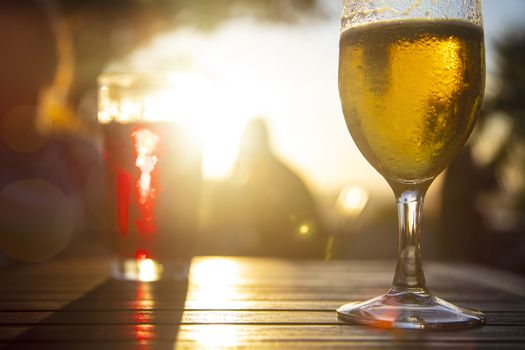 Red wine and cold beer against the sun with male silhouette at background