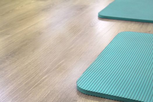 Yoga mat on wooden floor to perform meditation exercises