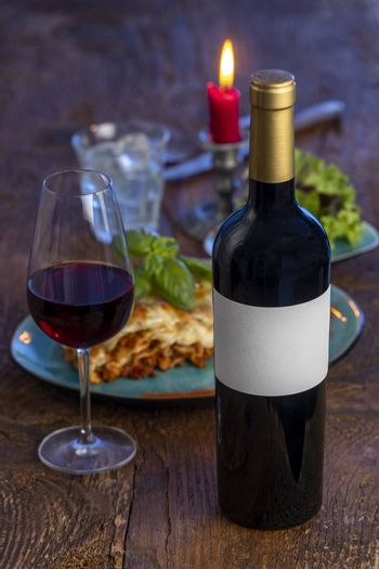 red wine and lasagna on wood