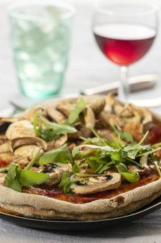 mushroom pizza on a plate with arugula