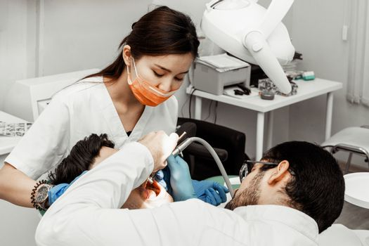 Two dentists treat a patient. Professional uniform and equipment of a dentist. Healthcare