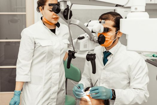 Two dentists treat a patient. Professional uniform and equipment of a dentist. Healthcare Dentistry.
