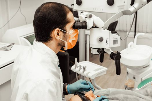 A young male dentist doctor treats a patient. Medical manipulations in dentistry, surgery. Professional uniform and equipment of a dentist. Healthcare