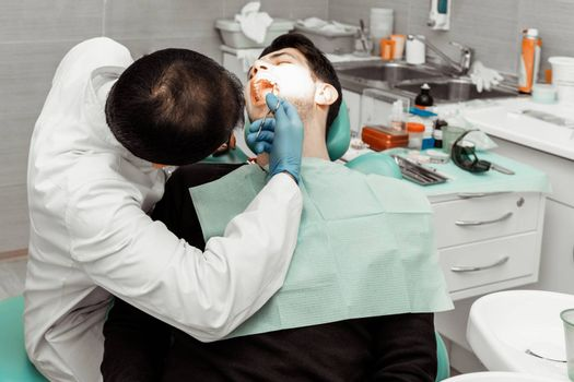 A young male dentist doctor treats a patient. Medical manipulations in dentistry, surgery. Professional