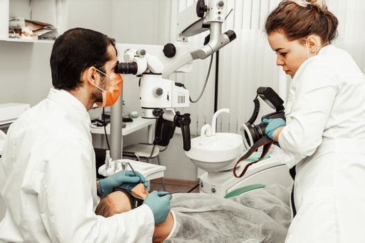 Two dentists treat a patient. Professional uniform and equipment of a dentist. Healthcare Equipping