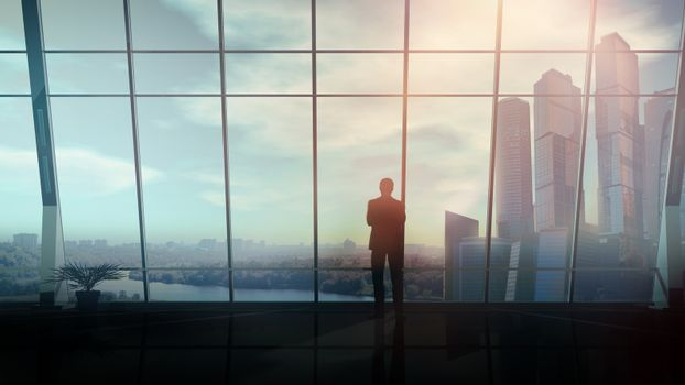 Opposite the panoramic window, a businessman stands and looks into the distance.