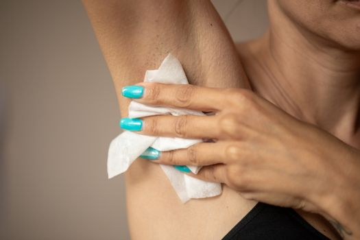 Old woman wipes the armpit with wet wipes