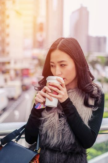 Woman drinking coffee at outdoor street with sunrise streaming