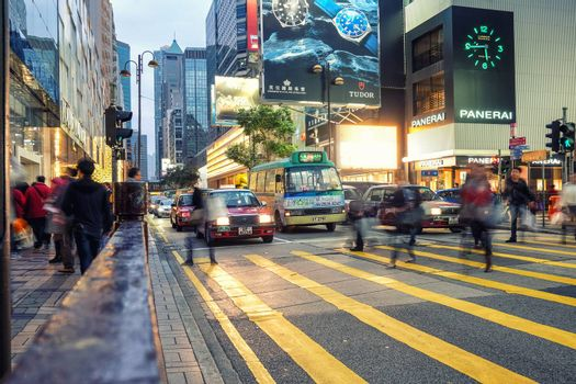 HONG KONG - JANUARY 14: People speed walking across Road, Causeway Bay in front of a big department store at Daylight. Hong Kong January 14, 2016
