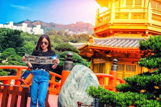 Young female tourist with map looking for a way to Gold Chinese pavilion Temple at the park in Hong Kong