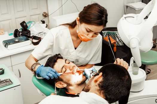 Two dentists treat a patient. Professional uniform and equipment of a dentist. Healthcare doctors workplace. Dentistry.
