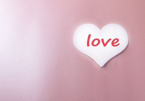 White background with paper heart and the words LOVE pink background heart, love, holiday greeting card, a minimum of creative idea of a holiday Valentine's day, space for copy.