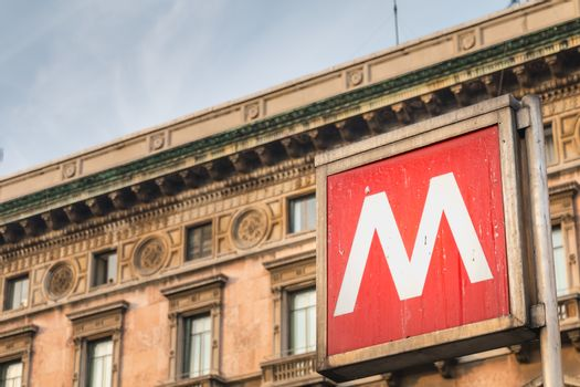 Milan, Italy - November 2, 2017: sign indicating the entrance to a metro station in the city center on a fall day
