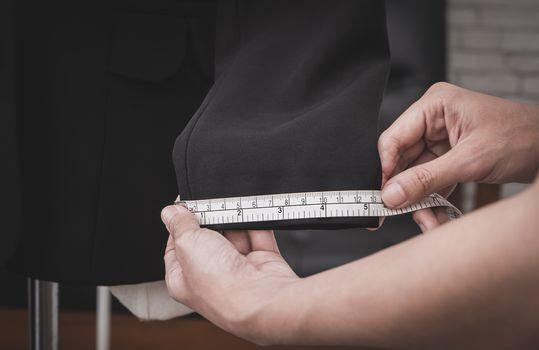 Clothing stylist is measuring jacket sleeve