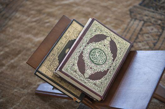 Koran prayer books on wooden stand in mosque