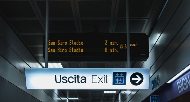 Milan, Italy - November 2, 2017: In the corridors of the subway, a bright billboards indicate the exit on a fall day